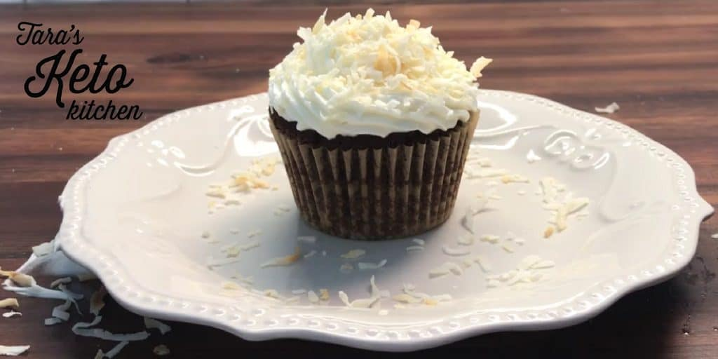 keto coconut frosting piped on top of a chocolate cupcake and garnished with toasted coconut flakes