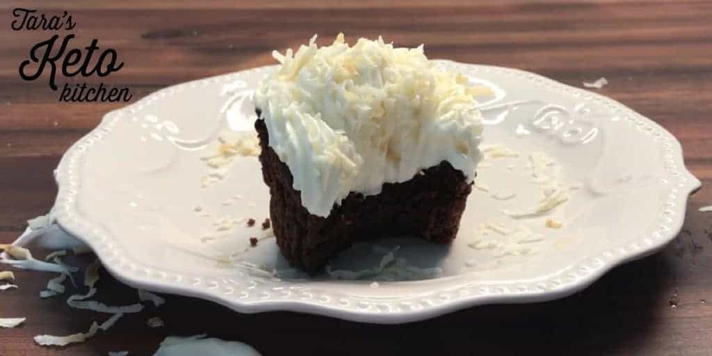 keto coconut frosting piped on a chocolate cupcake garnished with toasted coconut flakes with a bite taken out of it showing off the creamy texture