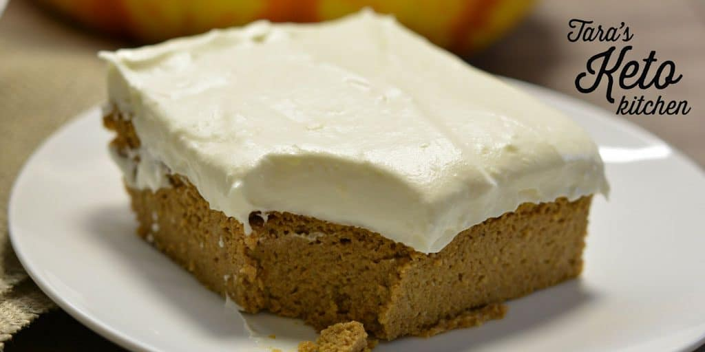 Keto Pumpkin Bars with Maple Cream Cheese Frosting on a white plate with a bite taken out to show the pumpkin pie esq texture