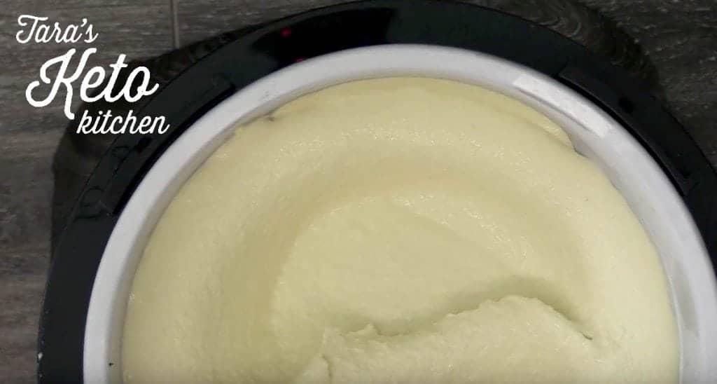 Keto Vanilla Ice Cream pictured frozen in an ice cream maker tub