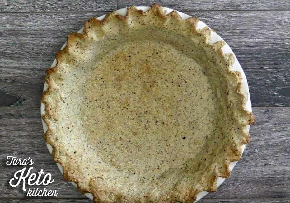 Keto Pie Crust with Hazelnut Flour shown baked with fluted edges in a pie pan