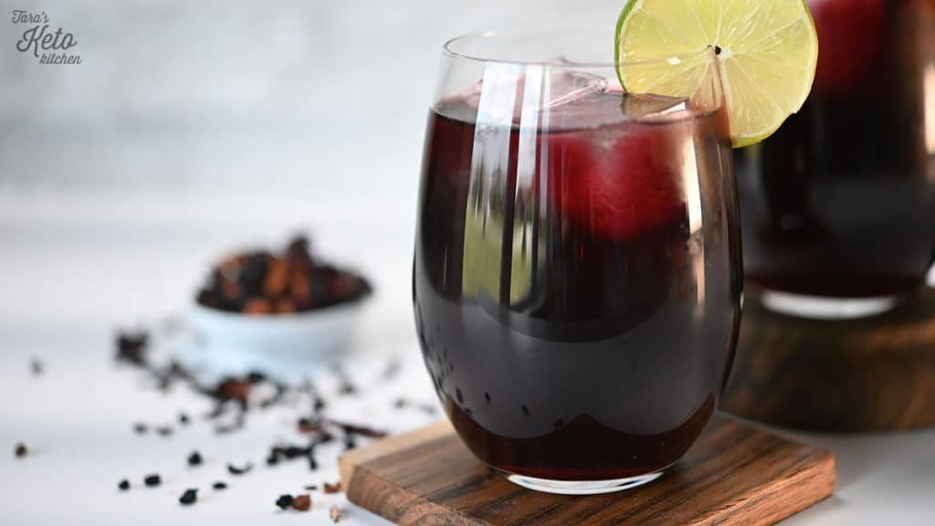 a wine glass with ice showing berry colored Low Carb Sangria with the pitcher full of sangria next to it