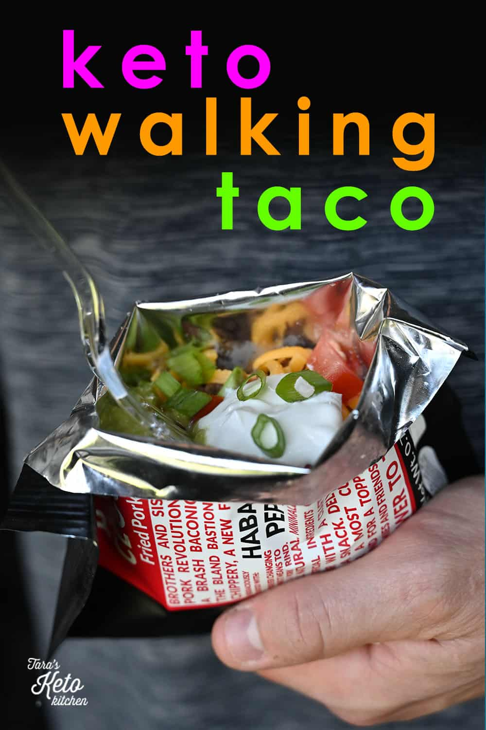 man holding a keto walking taco showing sour cream and green onion peeking out