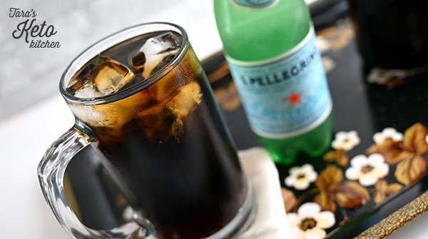 Low Carb Root Beer in a mug with sparkling water shown behind it