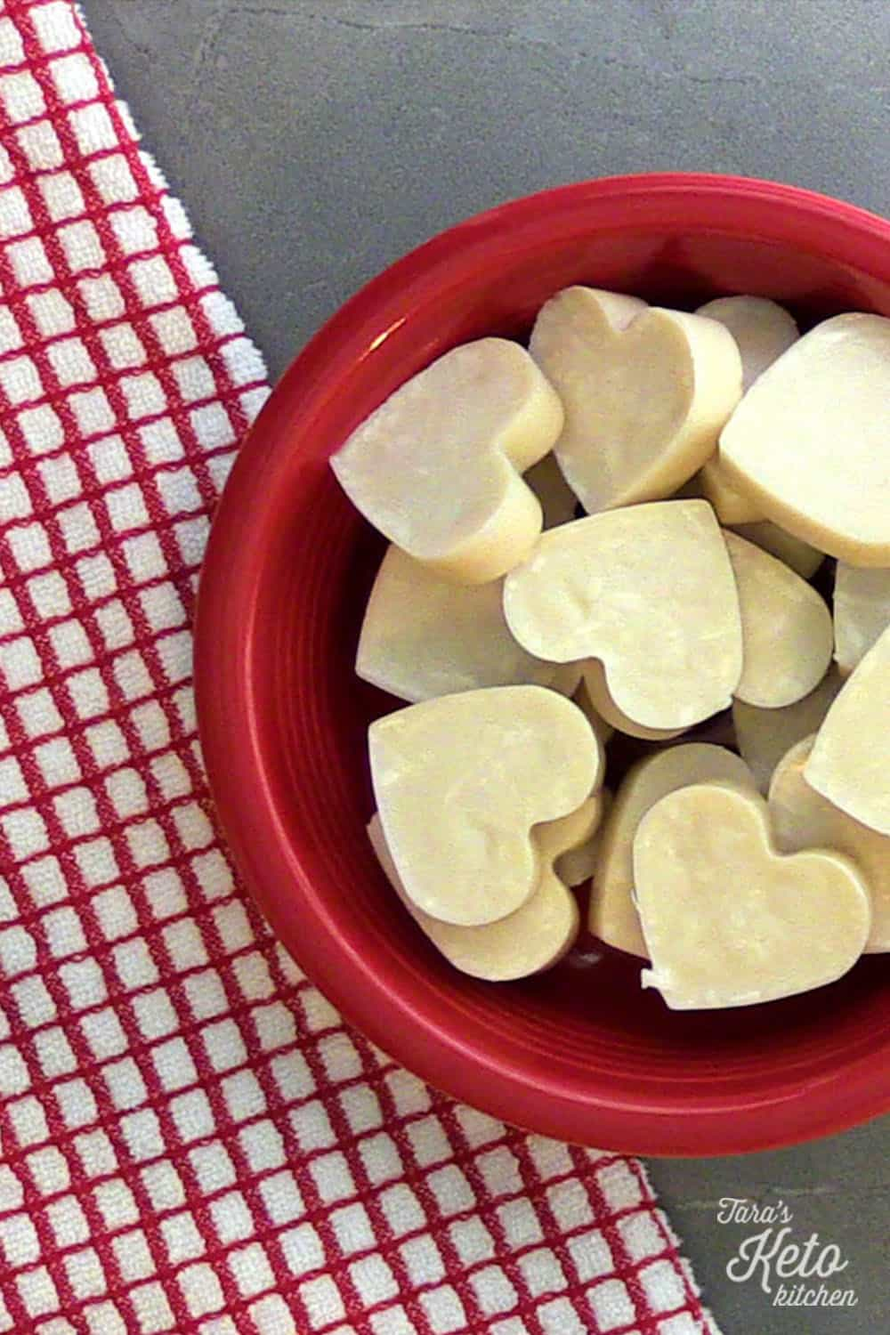 coconut fat bombs shaped like hearts in a red bowl